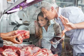 Couple Buying Meat At Butchery